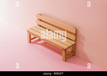 a wooden bench miniature. Pink Two Tone Background. - Stock Photo