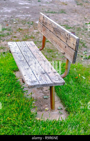 Wooden bench painted white on a grassy terrain - Stock Photo
