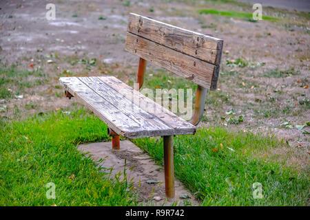Old wooden bench on grassy terrain in Provo Utah - Stock Photo