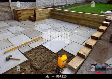 Indian paving slabs being laid on a garden patio garden renovation UK - Stock Photo