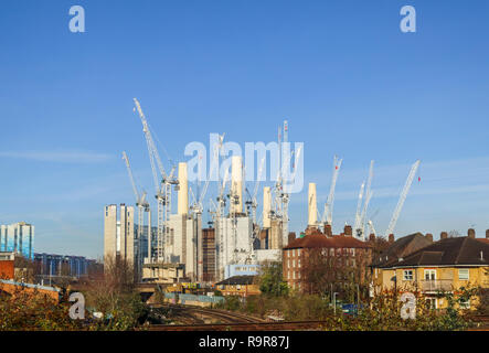 White tower cranes surround the iconic decommissioned Battersea Power Station being redeveloped for mixed uses and high class luxury apartments