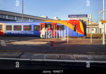 South Western Railway train by a platform name board at Clapham Junction railway station, south-west Battersea, London Borough of Wandsworth - Stock Photo