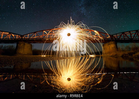 Light painting art concept. Spinning steel wool in abstract circle, firework showers of bright yellow glowing sparkles on long bridge reflected in riv - Stock Photo
