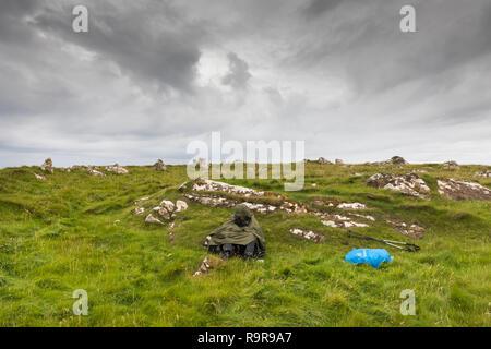 Person seeking protection against the rain, sitting on the grass. Fetlar, Shetland Islands. - Stock Photo