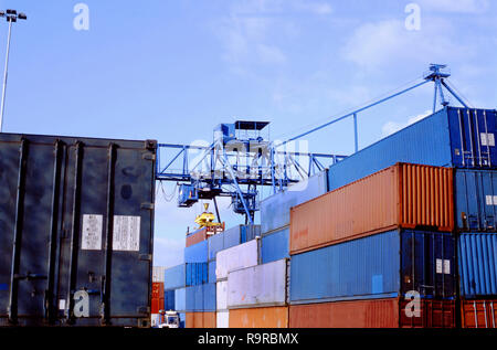 Stacked up shipping containers at container terminal in port of Rotterdam sea harbour. No brands or names. Only signs with informations about weight. - Stock Photo