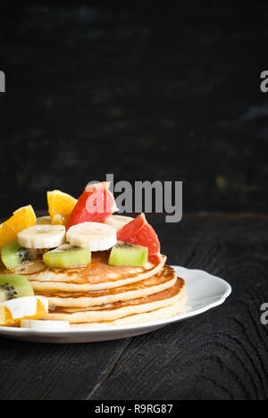 Plate of pancakes with fruits and honey at dark wooden table. - Stock Photo