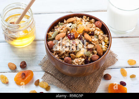 Granola cereal flakes with dried fruit, nuts and honey in a wooden bowl. - Stock Photo