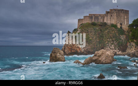 Fort Lovrijenac in Dubrovnic as seen from the beach on a stormy day, with crashing waves and dark cloud horizon - Stock Photo