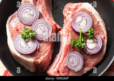 Two pieces of raw pork chops in a frying pan. - Stock Photo