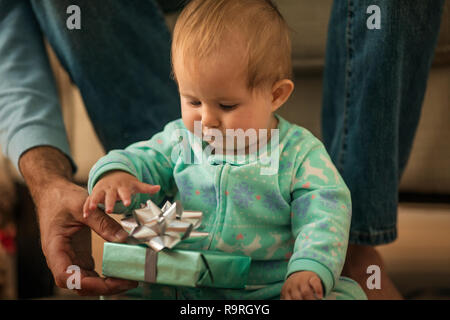Baby girl opening a present from her father. - Stock Photo