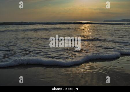 A line of foaming bubbles on a sandy beach at England's south coast, the famous white cliffs in silhouette as the sun sets and is reflected off the ca - Stock Photo