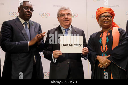(181227) -- BEIJING, Dec. 27, 2018 (Xinhua) -- Photo taken on Oct. 8, 2018 shows President of the International Olympic Committee (IOC) Thomas Bach (C) showing a card with Senegalese President Macky Sall (L) and Dakar Mayor Soham El Wardini during the 133rd IOC Session in Buenos Aires, capital of Argentina. Africa will welcome the continent's first Olympic event as Senegalese capital Dakar was selected by the International Olympic Committee as the host for the 2022 Youth Summer Olympic Games at the 133rd IOC Session on October 8. By then, the Olympic event will have been held on all six perman - Stock Photo