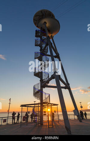Bournemouth, Dorset, UK. 27th Dec, 2018. Beautiful sunset over Bournemouth beach at the end of a lovely sunny day, as visitors head to the pier and beach to watch the sun go down. The spiral structure of the zipline zipwire launch tower on Bournemouth Pier silhouetted with sunburst. Credit: Carolyn Jenkins/Alamy Live News - Stock Photo