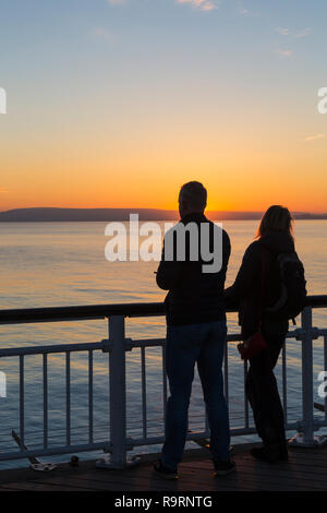 Bournemouth, Dorset, UK. 27th Dec, 2018. Beautiful sunset over Bournemouth beach at the end of a lovely sunny day, as visitors head to the pier and beach to watch the sun go down. Couple. Credit: Carolyn Jenkins/Alamy Live News - Stock Photo
