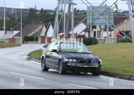 Inverness, Scotland, UK. 28 December 2018. Police in Inverness are trying to trace the driver of a black BMW that was involved in a single-vehicle collision over Christmas. The abandoned vehicle was reported to police on Boxing Day and was still in situ on Essich Road two days later with crime scene tape wrapped around it. There is substantial damage to the front of the vehicle and the nearside door mirror, and the driver's window is partially open. Picture Credit: Andrew Smith/Alamy Live News - Stock Photo