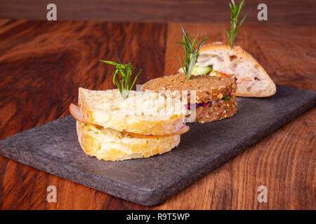Three sandwiches with salad, ham, cheese and tomatoes on marble table. - Stock Photo