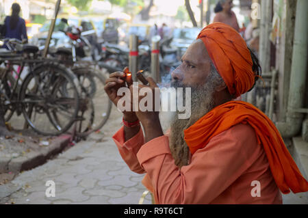 A sadhu or holy man, a follower of Hindu god Shiva, smoking hashish or cannabis in a street in Mumbai, India, cannabis being associated with Shiva - Stock Photo