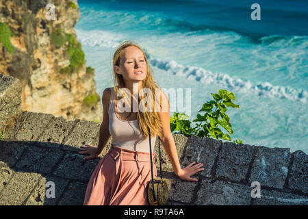 Young woman traveler in Pura Luhur Uluwatu temple, Bali, Indonesia. Amazing landscape - cliff with blue sky and sea - Stock Photo
