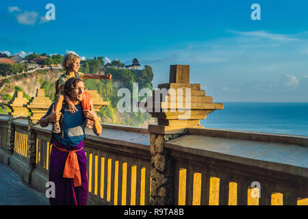 Dad and son travelers in Pura Luhur Uluwatu temple, Bali, Indonesia. Amazing landscape - cliff with blue sky and sea. Traveling with kids concept - Stock Photo