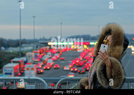 Pictured: A woman stands on a bridge to take a selfie on her mobile phone while long queues of cars form by the Severn Bridge tolls on the westbound c - Stock Photo
