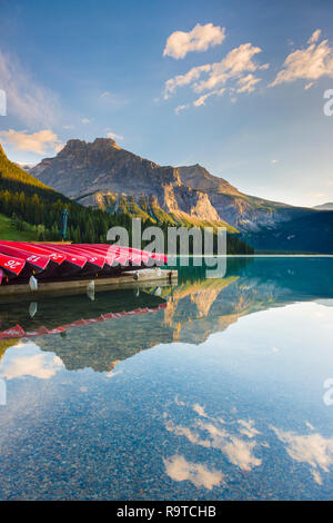 An early morning for a tourist free golden sunrise & stunning views across to the distant mountains reflected the mirror calm glacial fed lake water - Stock Photo