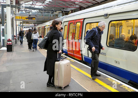 People waiting on the platform with luggage boarding a Hammersmith and City tube train in an underground station in London England UK  KATHY DEWITT - Stock Photo