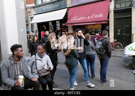 Borough Market street scene people drinking coffee and walking outside Konditor & Cook cake shop and Monmouth coffee shop London UK  KATHY DEWITT - Stock Photo