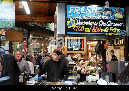 Trader selling fresh cooked hand gathered Mussels on a Borough Market seafood stall in South London England UK  KATHY DEWITT - Stock Photo
