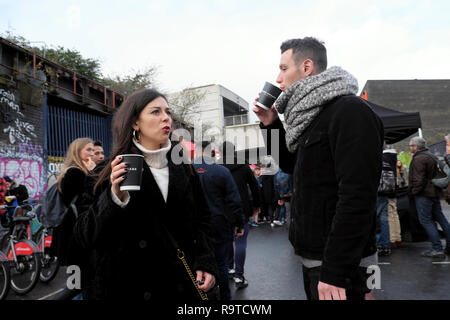 People visiting Brick Lane East End young couple standing in the street drinking hot coffee in winter in Shoreditch East London E1 UK  KATHY DEWITT - Stock Photo
