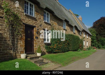 Row of picturesque stone built thatched cottages in the village of Ashby St Ledgers, Northamptonshire, UK - Stock Photo