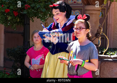 Orlando, FL USA. Feb 2016. A girl`s curiosity look at Snow White while signing her Memory Maker book at Disney World. - Stock Photo