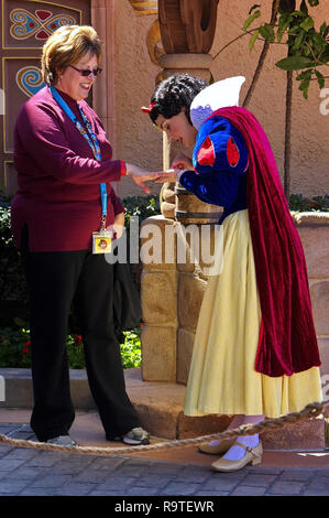 Orlando, FL USA. Feb 2016. Snow White takes a short break to look at a co-worker`s engagement ring at Disney World. - Stock Photo