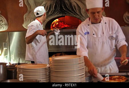 Orlando, FL USA. Feb 2016. Chef preparing wood fired oven with another cutting an already cooked pizza. - Stock Photo