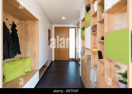 Custom made colorful wooden shelves in the hall of modern house