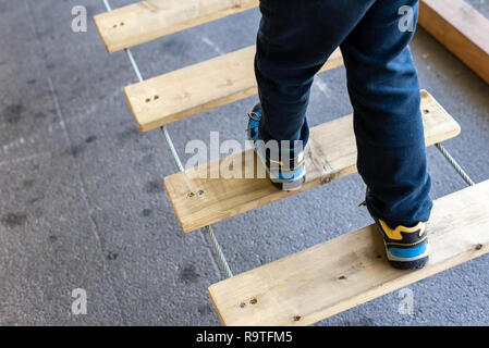 Foot of child doing balances on wooden boards in an urban adventure park. - Stock Photo