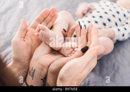 partial view of parents holding little babys feet in hands together - Stock Photo