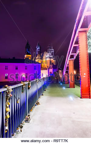 Poznan, Poland - December 26, 2018: Metal barrier on the Jordan bridge by night over the Warta river with cathedral building in the background. - Stock Photo