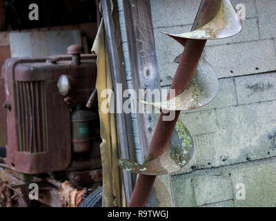 Antique tractor and rusty blades of farm equipment - Stock Photo