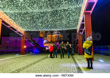 Poznan, Poland - December 26, 2018: Woman taking a photo of a couple on the Jordan bridge with decoration lamps during the Christmas holiday season by night. - Stock Photo