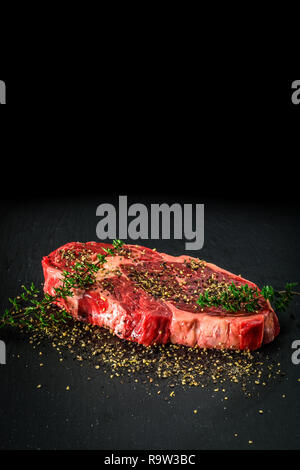 Raw dry aged entrecote steak. Delicious barbecure rib eye steak with different spices on a dark stone plate. - Stock Photo