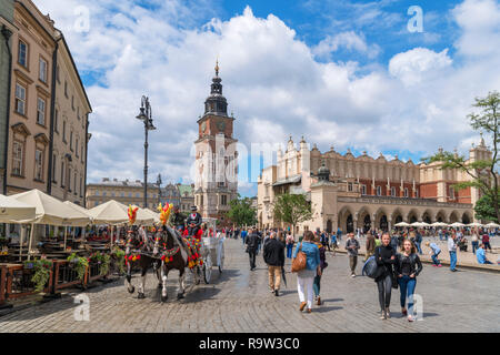 Horse and Carriage ride in front of the Town Hall Tower (Wieża ratuszowa) & Cloth Hall (Sukiennice) in the Main Square (Rynek Główny), Kraków, Poland - Stock Photo