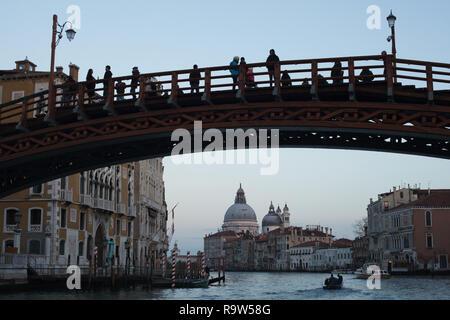 Accademia Bridge (Ponte dell'Accademia) and the Basilica of Santa Maria della Salute (Basilica di Santa Maria della Salute) on the Grand Canal (Canal Grande) in Venice, Italy, pictured from a boat. - Stock Photo