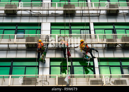 Occupation: repairmen suspended by cables at building exterior in Shenzhen, China - Stock Photo