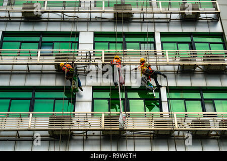 Occupation: repairmen suspended by ropes at building exterior in Shenzhen, China - Stock Photo