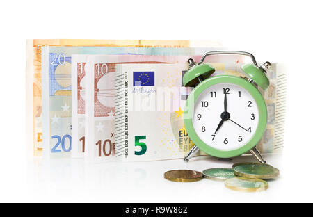 Green alarm clock on the background of europrints and coins. Isolated on white background. - Stock Photo