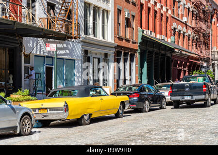 New York City, USA - June 25, 2018: Street scene with classic yellow Cadillac Eldorado convertible car in Tribeca District of Manhattan a sunny day of - Stock Photo