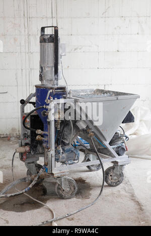 Plastering machine for house plastering walls. Electric Spray Plaster Machine. Automatic cement wall screeding plaster machine. - Stock Photo