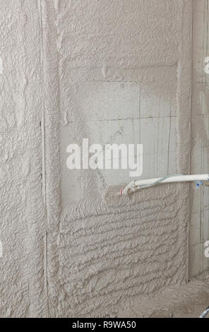 Plastering wall with spray plastering  machine for house plastering walls. Automatic cement wall screeding plaster machine. - Stock Photo