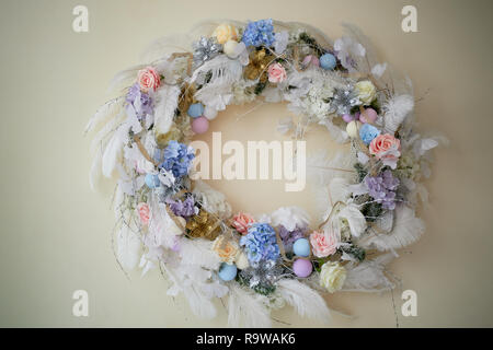 Decoration for the interior.Wreath of blue and white scale of feathers and flowers on a light wall background. - Stock Photo