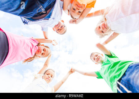 Lovely schoolchildren standing in a circle holding hands up - Stock Photo